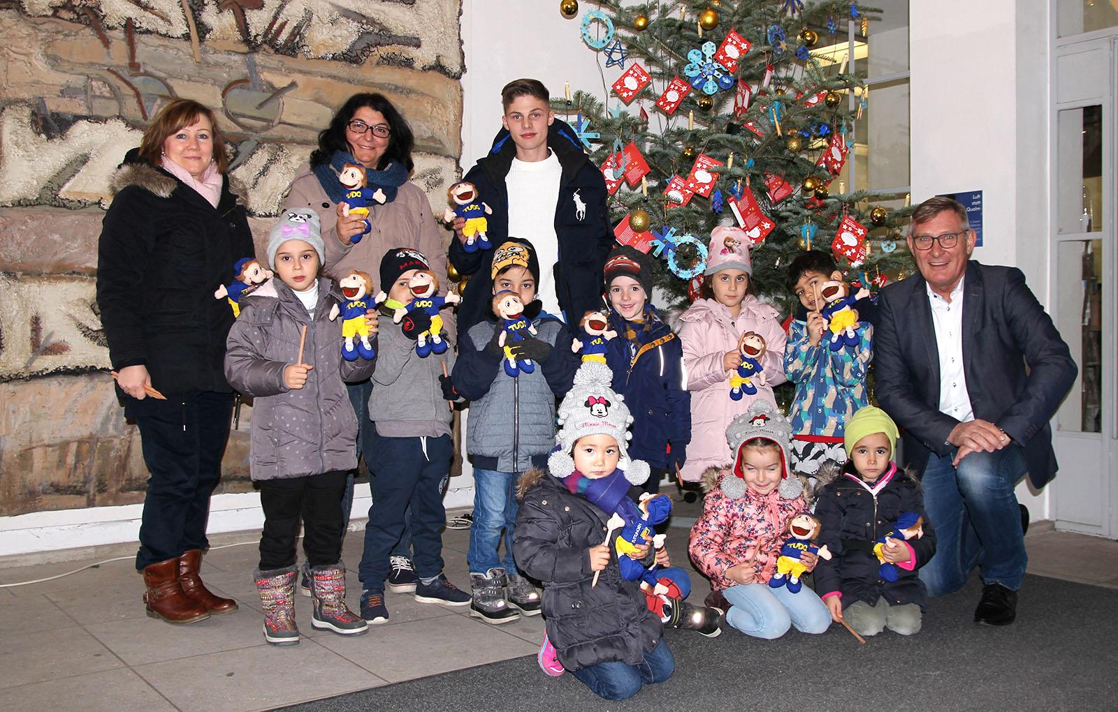 OB Beck mit Kindern vor einem Weihnachtsbaum