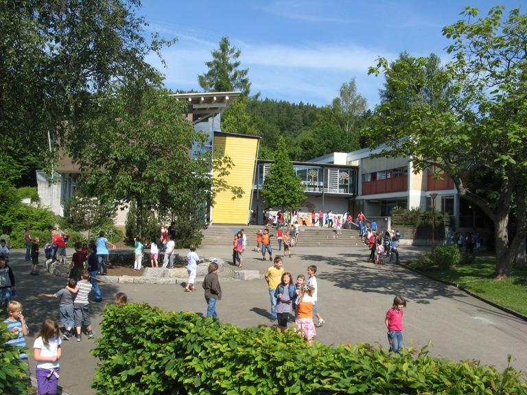 Ein Foto der Schildrainschule mit Blick auf den Schulhof und spielende Kinder