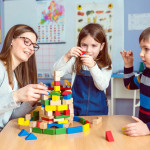 Kinder spielen mit Erzieherin