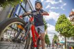 Bild von einem Jungen auf einem roten Fahrrad