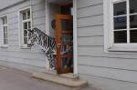 Ein Zebra aus Holz schaut aus der Eingangstür der Jugendkunstschule heraus