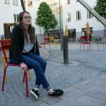 Junge Frau sitzt auf einem Stuhl auf dem Marktplatz