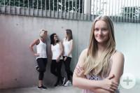 Sarah Fix im Vordergrund _ im Hintergrund stehen drei Kolleginnen an einer Mauer