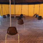 Bild mit versetzter Bestuhlung im Zelt vor Bühne und offenen Seitenwänden
