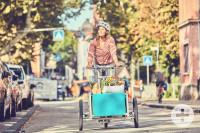 Frau auf Lastenrad beladen mit Einkäufen fährt eine Straße entlang