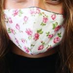 Eine junge Frau trägt Maske mit Blümchen