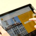 Jemand hält ein Tablet in Händen, auf dem die Startseite der städtischen Homepage zu sehen ist