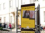 Plakatständer in der Fußgängerzone mit Plakat zur Maskenpflicht