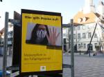 Plakat zur Maskenpflicht mit dem Rathaus im Hintergrund