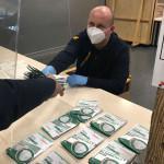 Ein Mann mit Maske überreicht Masken an einen Abholer