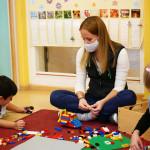 Erzieherin sitzt mit Kindern im Kindergarten