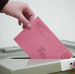 Person steckt einen Wahlbrief in die Wahlurne