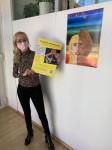 Gleichstellungsbeauftragte Lucia Faller zeigt das Plakat zur Ausstellung anlässlich des Weltfrauentags.