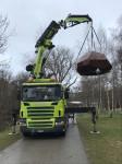 Ein grüner LKW hebt mit seinem Kran die Skulptur