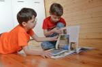Zwei Jungs blättern in einem Buch mit Bildern.