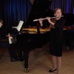 Musikschülerin spielt Querflöte und wird von Lehrerin am Flügel begleitet