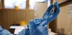 Eine Person mit blauen Gummihandschuhen zieht eine Impfspritze auf.