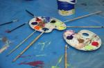 Zwei Malpaletten und Pinsel liegen auf einer blauen Unterlagen mit Farbspritzern.