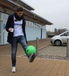 Fußballspieler jongliert grünen Ball