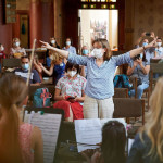 Musiklehrerin mit Munschutz dirigiert Orchester vor Publikum