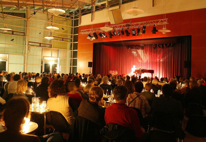 Blick auf die Bühne in der Angerhalle im Vordergrund das Publikum, auf der Bühne spielt jemand Klavier.