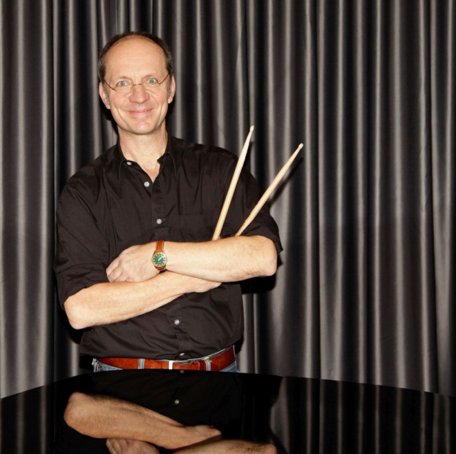 Bild Karl Koch mit verschränkten Armen und Schlagzeugstöcken in der rechten Hand