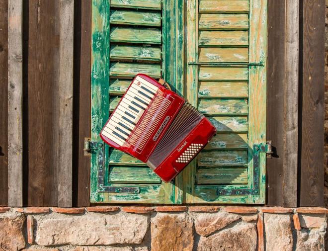 Rotes Akkordeon vor grünem Fensterladen
