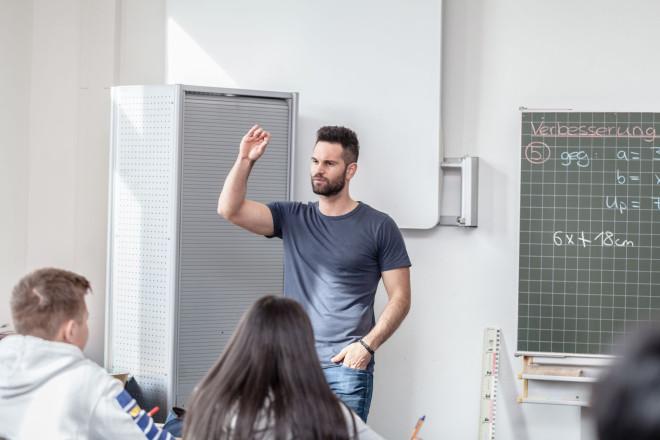 Ein Lehrer steht an der Tafel und unterrichtet
