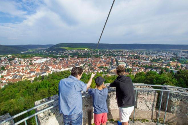 Drei Personen stehen auf dem Zinnenturm des Honbergs und schauen auf Tuttlingen