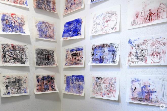 Bild aus dem Online-Kreativprogramm vom April 2020, viele von Kindern bunt gemalte Bilder hängen an weißen Wänden – Blick in die Ecke