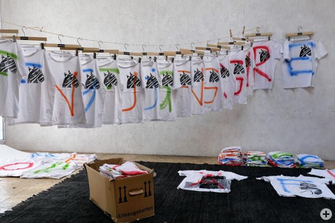 16 weiße T-Shirts, bunt bemalt mit Zebras, hängen jeweils an einem Kleiderbügel, nebeneinander an Wäscheleine