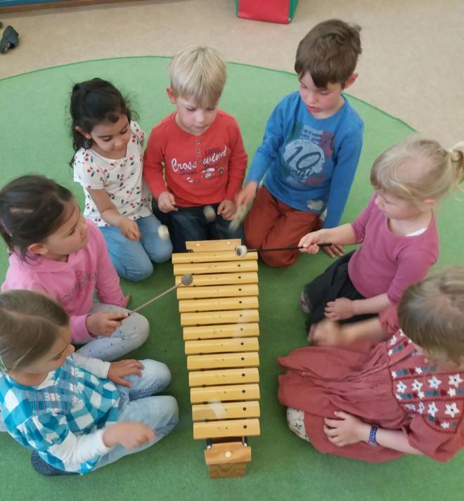 Bild aus der Musikalischen Früherziehung auf dem mehrere Kinder um ein Xylophon sitzen