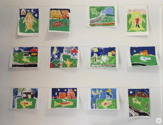 Bild aus dem Online-Kreativprogramm der Woche 5, zwölft von Kindern bunt gemalte Bilder hängen an weißer Wand