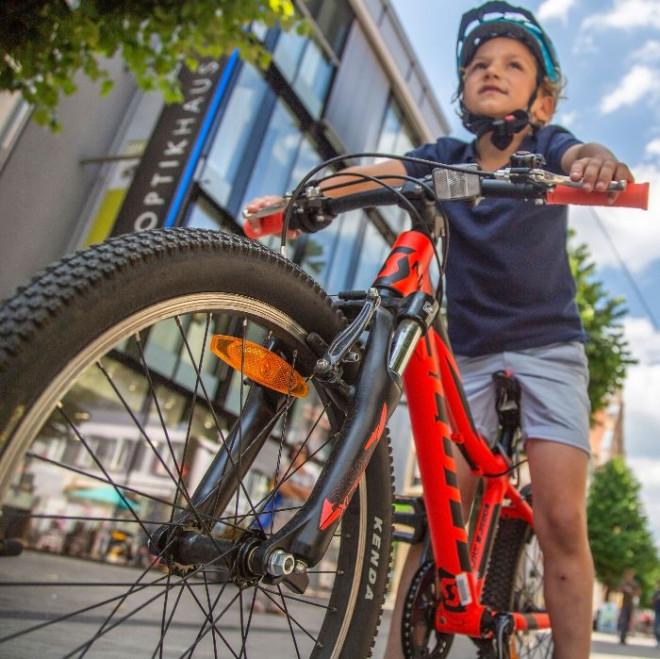 Kind mit Helm auf einem roten Fahrrad