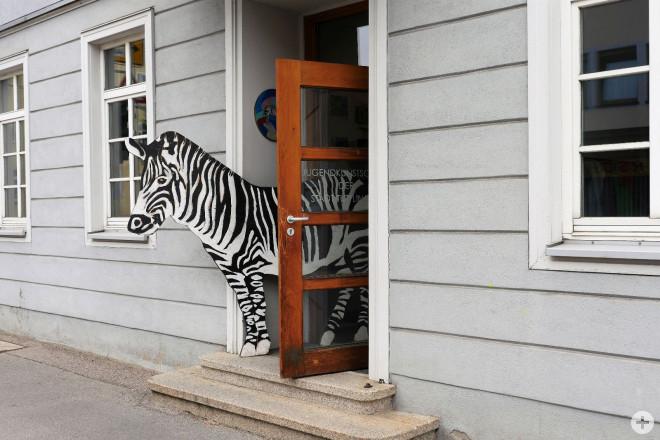 Foto aus dem Online-Kreativprogramm der Woche KW 23 – großes gebasteltes Zebra am Haupteingang der Jugendkunstschule