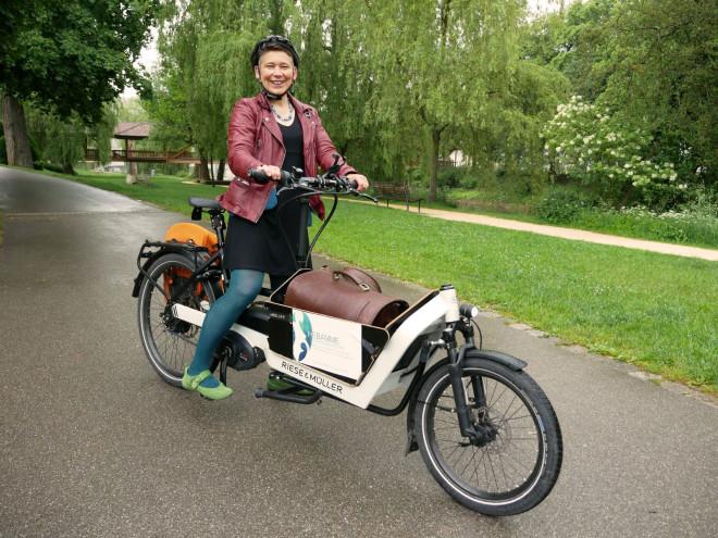 Stadträtin Katja Rommelspacher sitzt auf ihrem Lasten-Fahrrad am Donauufer