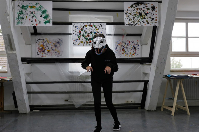 Foto aus dem Online-Kreativprogramm der Woche KW24 – Schülerin mit selbstgebasteler Maske aus Alufolie steht vor bunt gemalten Bildern