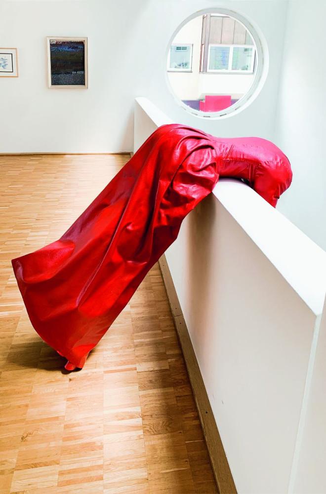 Werk der Künstlerin Luithle (Rotes Kleid) ist über die Balustrade in der Galerie gelehnt