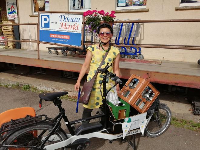 Katja Rommelspacher steht neben ihrem mit Getränkekisten beladenen Lastenrad