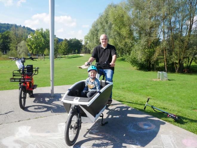 Vater und Sohn auf einem Cargobike im Donaupark