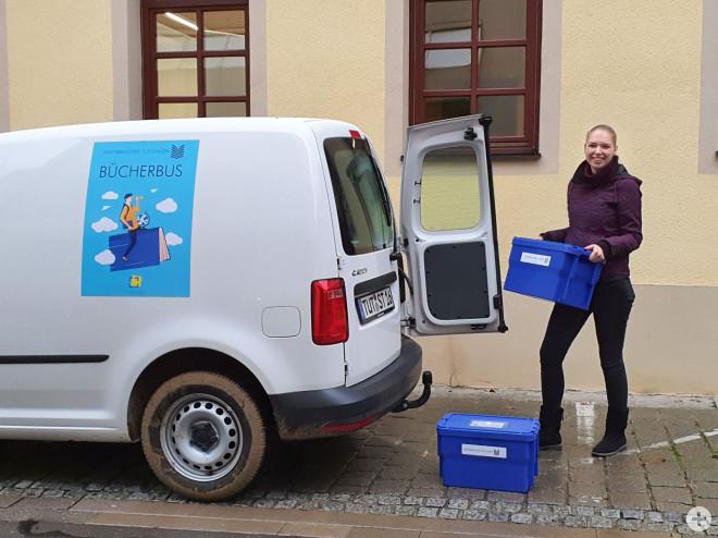 Bücherbus mit Mitarbeiterin beim Beladen der Bücherkisten