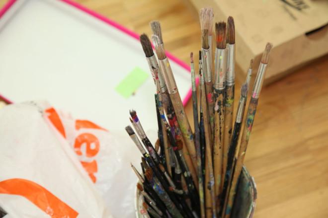 Becher mit mehreren gebrauchten Farbpinsel
