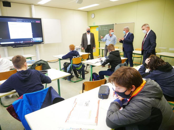 Ob Michael Beck, Minister Wolf, Schulleiter Schwarz und ein Lehrer stehen vor eine Klasse im OHG