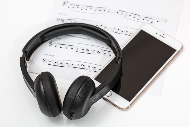 Smartphone mit Kopfhörer auf Notenblatt