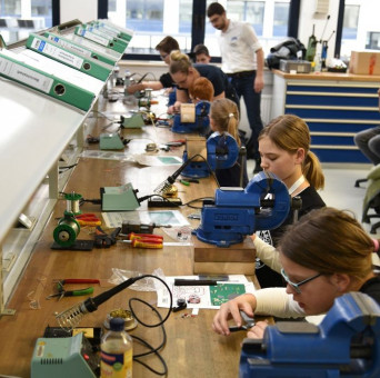 Mehrere Schüler arbeiten in der Laborwerkstatt an der Werkbank