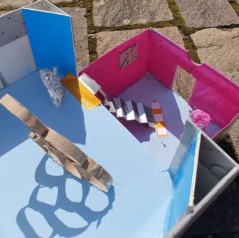 Kunstwerk von Kindern – Blick von oben in ein bunt bemaltes Haus aus Karton