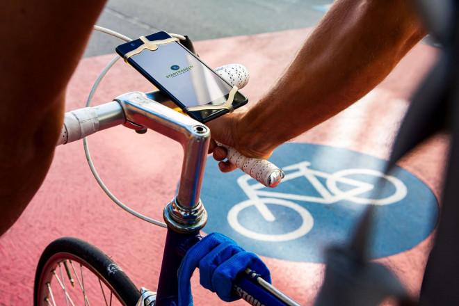 Smartphone mit der geöffneten Stadtradeln-App ist an einem Fahrradlenker befestigt.
