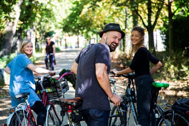 Zwei Frauen und ein Mann mit Fahrrad lächeln in die Kamera.