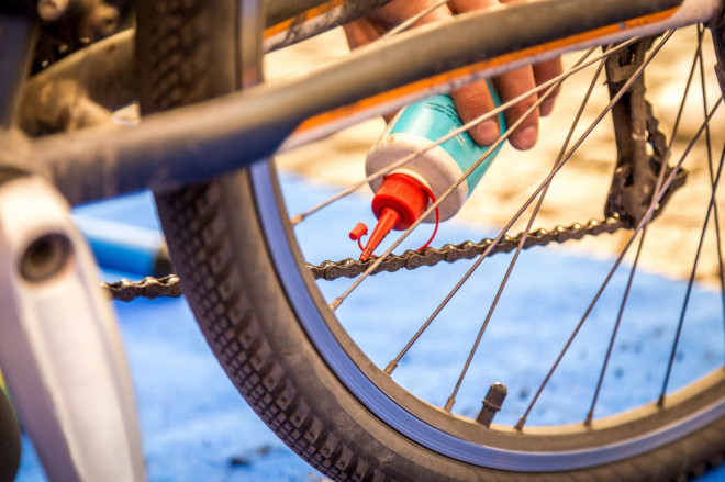 Jemand macht Öl auf eine Fahrradkette beim RadCheck.