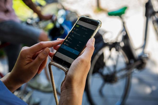 Jemand hält ein Smartphone in der Hand, auf dem die Stadtradeln-App geöffnet ist. Im Hintergrund sind Fahrräder zu sehen.